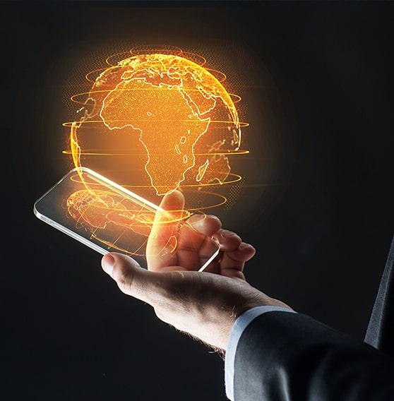 Mano sosteniendo un móvil que a su vez sostiene una bola del mundo
